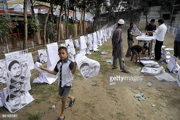 A Bangladeshi child carries a poster as political supporter prepare election campaign material in old Dhaka on December 21 2008 A general election is...