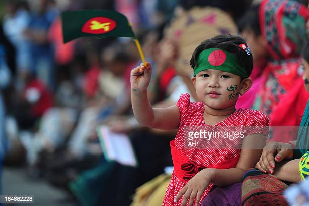 A Bangladeshi child holds a national flag as she attends a rally with her mother to mark the 42nd anniversary of independence in Dhaka on March 26...