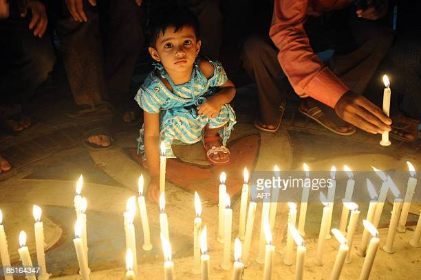 A Bangladeshi child joins in as people light candles during a remembrance gathering for people killed during the recent mutiny at the Bangaldesh...