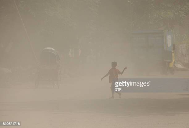 Bangladeshi child walks along a dusty road in Dhaka on September 27 2016 / AFP / STR