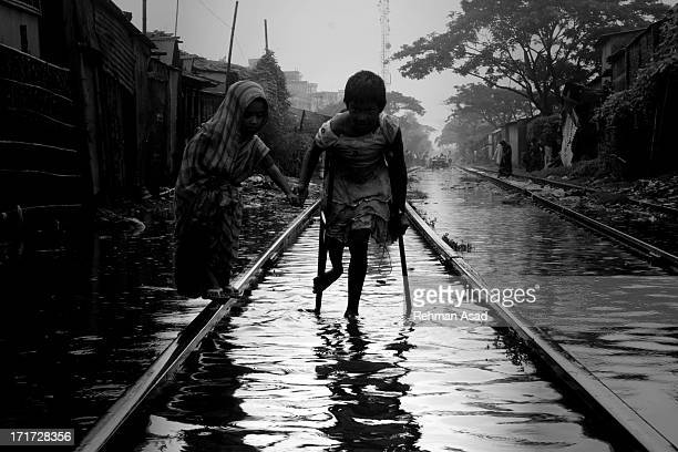 Bangladeshi Children one who disable is walking risky while rail line sunk by heavy rainfall during the monsoon season in Dhaka.