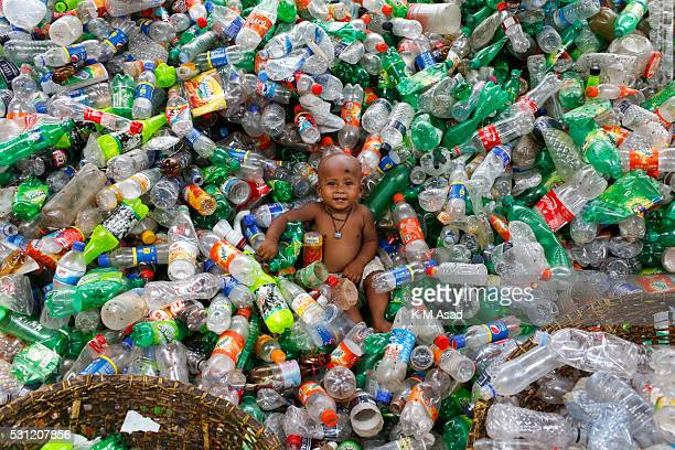 Bangladeshi children sits amid empty bottles where women labourers sift through empty bottles at a plastic bottle recycling centre in Dhaka...