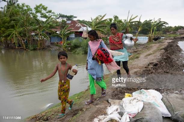 Bangladeshi children walk over the top of a sandbag embankment that was breached by high waters in Khulna on May 4 as Cyclone Fani reached Bangladesh