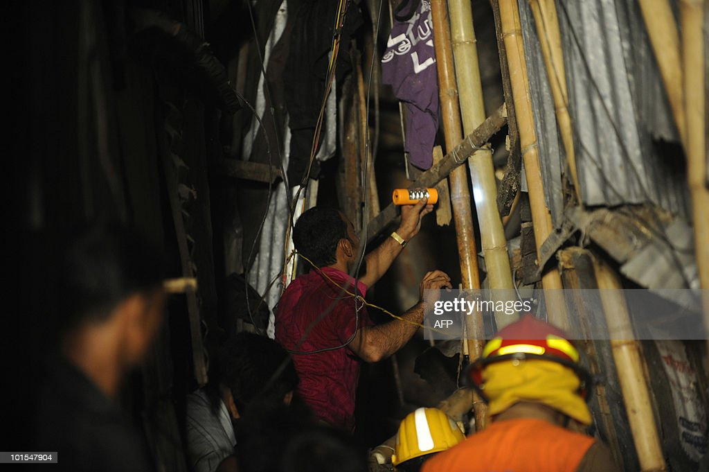 A Bangladeshi civilian looks for trapped survivors after a four-storey building collapsed in Dhaka late on June 1, 2010. A four-storey building collapsed late on June 1 and fell on several tin-roofed shanties in Dhaka, trapping an unknown number of people, police and fire officials said.