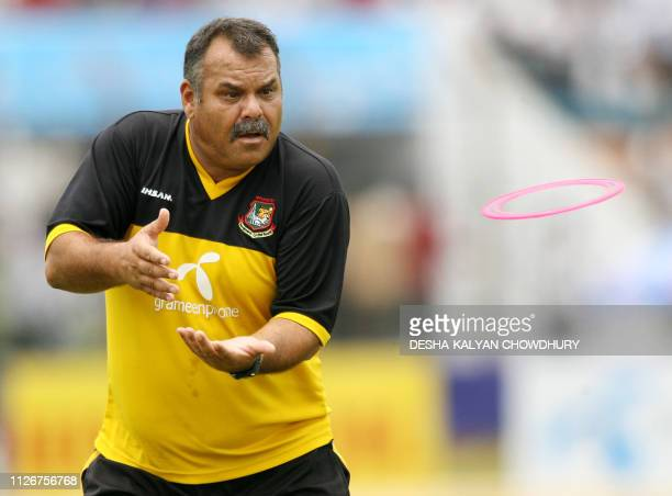 Bangladeshi coach Dev Whatmore prepares to catch a disk during a practice secession at the Ruhul Amin stadium in Chittagong 22 May 2007 Damp ground...