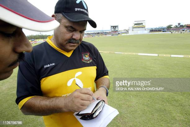 Bangladeshi coach Dev Whatmore signs an autograph prior to the start of the first cricket Test match between Bangladesh and India at the Ruhul Amin...