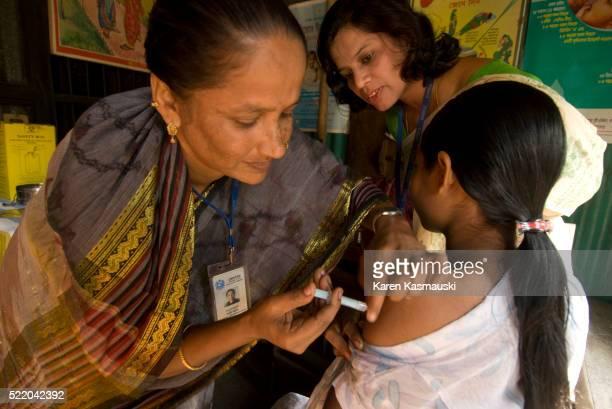 Bangladeshi community health worker giving vaccination