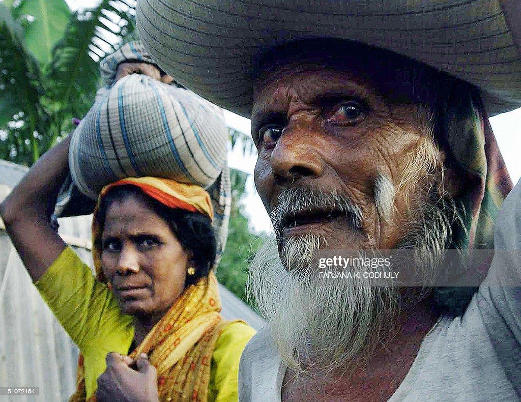 A bangladeshi couple carry bags of rice news photo