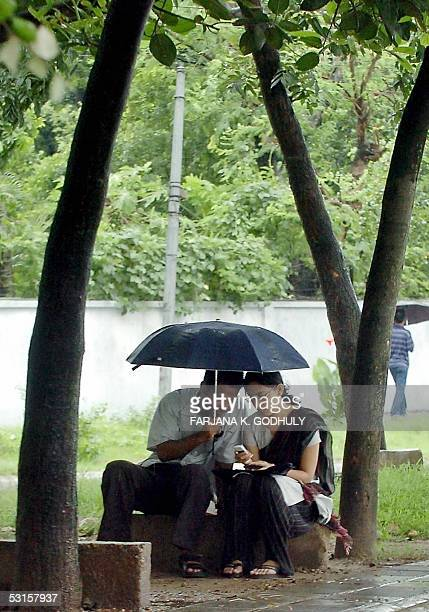 Bangladeshi couple play with their mobile phone while sitting under a moonsoon rain in Dhaka 28 June 2005 Meteorologists in Bangladesh blamed global...