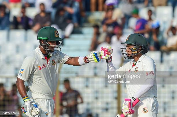 Bangladeshi cricket captain Mushfiqur Rahim celebrates with Sabbir Rahman after scoring a half century during the first day of the second cricket...