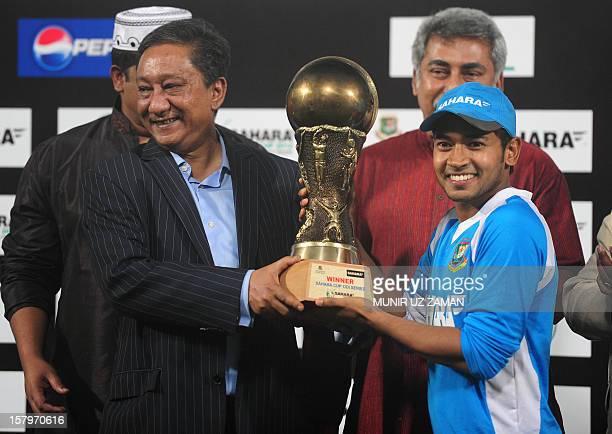 Bangladeshi cricket captain Mushfiqur Rahim holds the champion trophy from the Bangladesh Cricket Board president Nazmul Hasan Papon following a...