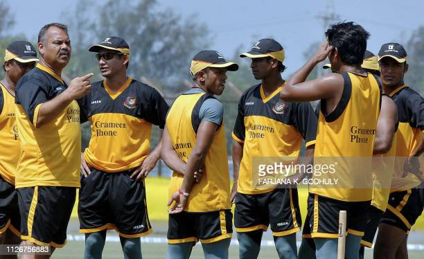 Bangladeshi cricket coach Dev Whatmore and team captain Habibul Bashar speak with team members during a practice session at The Bir Shererstha Ruhul...