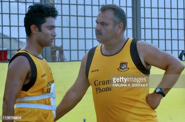 Bangladeshi cricket coach Dev Whatmore speaks with cricketer Nafis Iqbal during a practice session at The Bir Shrestha Shahid Ruhul Amin Stadium in...