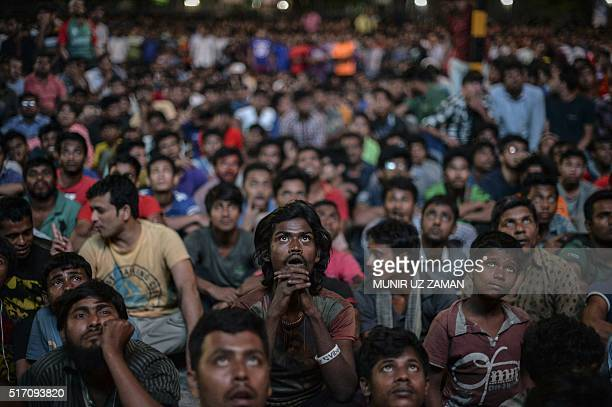 Bangladeshi cricket fan watch the World T20 cricket tournament match between Bangladesh and India broadcast on a screen in a street in Dhaka on March...