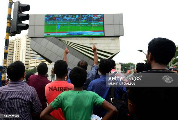 Bangladeshi cricket fans cheers as they watch the ICC Champions Trophy cricket match between Bangladesh and India broadcast on a screen in a street...