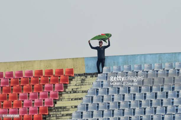 Bangladeshi cricket spectator weaves Bangladesh national flag during the fifth and final day of the first cricket Test between Bangladesh and Sri...
