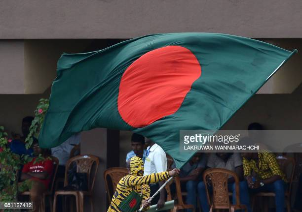 A Bangladeshi cricket supporter with his face painted in the style of a tiger waves his national flag during the fourth day of the opening Test match...