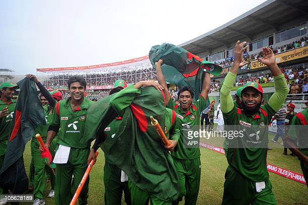 Bangladeshi cricket team captain Shakib Al Hasan covers his face to celebrate with his teammates after winning the match after the last...