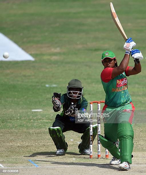 Bangladeshi cricketer Ayesha Rehman plays a shot as Pakistani wicketkeeper Rabiya Shah looks on during the second and final women's One Day...