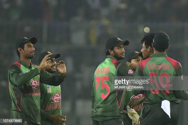 Bangladeshi cricketer congratulate teammate Mustafizur Rahman after the dismissal of the West Indies cricket captain Carlos Brathwaite during the...