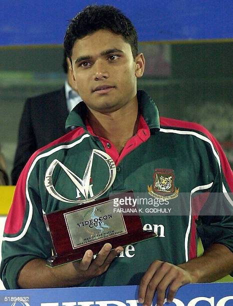 Bangladeshi cricketer Mashrafe bin Murtaza holds the Man of the Match trophy as he poses for photographers following his team's victory over India at...