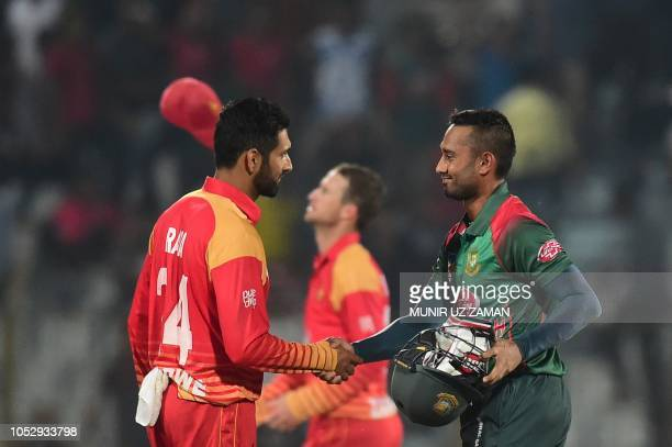 Bangladeshi cricketer Mohammad Mithun shakes hand with Zimbabwe's cricketer Sikandar Raza after winning the second one day international cricket...