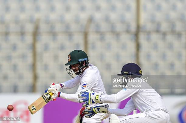 Bangladeshi cricketer Mominul Haque plays a shot as the Sri Lankan wicketkeeper Niroshan Dickwella during the fifth and final day of the first...