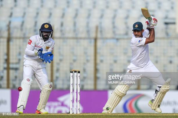 Bangladeshi cricketer Mosaddek Hossain plays a shot as the Sri Lanka wicketkeeper Niroshan Dickwella looks on during the fifth and final day of the...