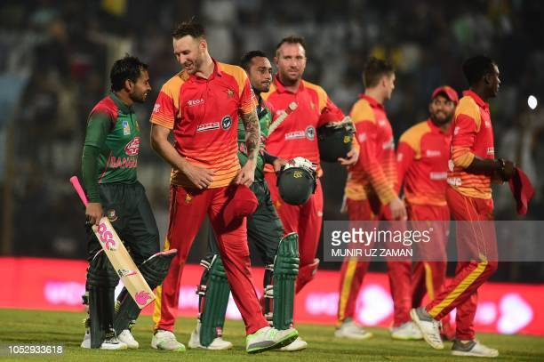 Bangladeshi cricketer Mushfiqur Rahim talks to Zimbabwe's cricketer Kyle Jarvis after winning the second one day international cricket match between...