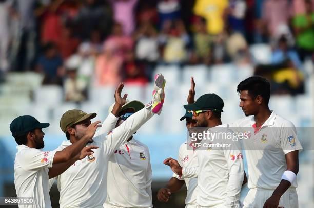 Bangladeshi cricketer Mustafizur Rahman celebrates with teammates after the dismissal of Australian cricketer David Warner during the fourth day of...