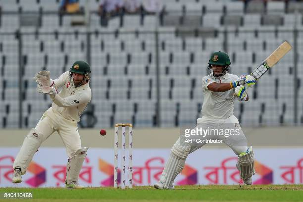 Bangladeshi cricketer Sabbir Rahman plays a shot as the Australian wicketkeeper Matthew Wade looks on during the third day of the first Test cricket...