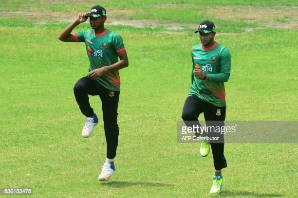 Bangladeshi cricketer Shakib Al Hasan and Mustafizur Rahman jog during a training session at the ShereBangla National Cricket Stadium in Dhaka on...