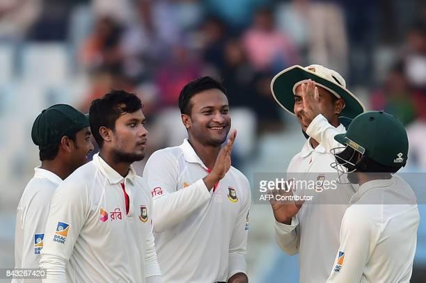 Bangladeshi cricketer Shakib Al Hasan celebrates with teammates after the dismissal of Australian cricketer Ashton Agar during the third day of the...