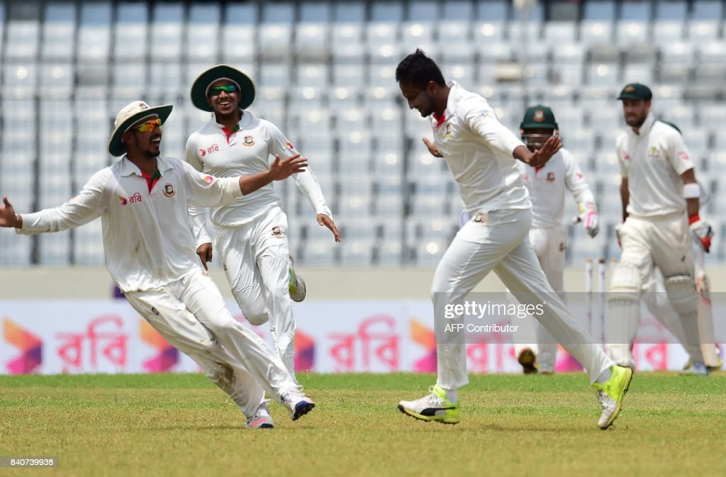 Bangladeshi cricketer Shakib Al Hasan (C) reacts after the dismissal of Australian cricketer Glenn Maxwell (R) during the fourth day of the first Test cricket match between Bangladesh and Australia at the Sher-e-Bangla National Cricket Stadium in Dhaka on August 30, 2017. / AFP PHOTO / Munir UZ