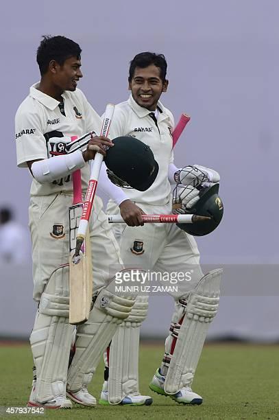 Bangladeshi cricketer Tajul Islam and captain Mushfiqr Rahim walk off the field after their team's win during the third day of the first cricket Test...
