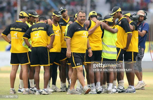 Bangladeshi cricketers huddle as coach Dev Whatmore walks at the Ruhul Amin stadium in Chittagong 22 May 2007 Damp ground conditions after overnight...