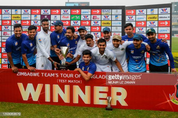 Bangladeshi cricketers pose for photos with the trophy following a presentation ceremony after winning the test match between Bangladesh and Zimbabwe...