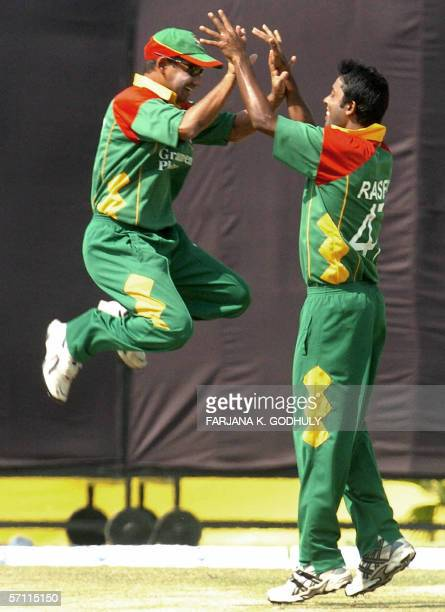 Bangladeshi cricketers Syed Rassel and Habibul Bashar celebrate the dismissal of unseen Kenyan batsman Stephen Tikolo during the first One Day...