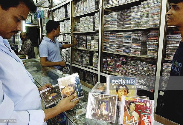 Bangladeshi customer looks at music CDs of Indian legendary singer Lata Mangeshkar 28 September 2003 at a music store in Dhaka The popular Indian...