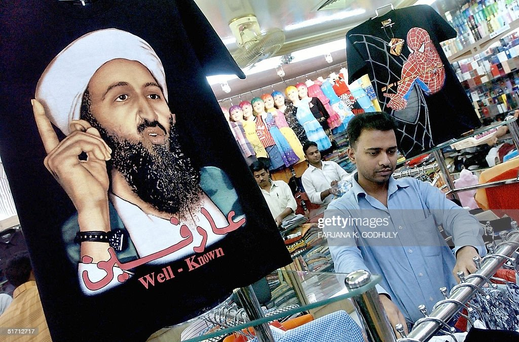 A Bangladeshi customer looks at shirts on display next to T-shirts bearing a portrait of Osma bin Laden and one of US superhero Spiderman at a shop in Dhaka, 10 November 2004. Bangladeshi Muslims started shopping for new clothes to wear at Eid-al Fitr celebrations, marking the end of the Islamic holy month of Ramadan, which falls this year in most of Asia on 14 November. AFP PHOTO/Farjana K. GODHULY