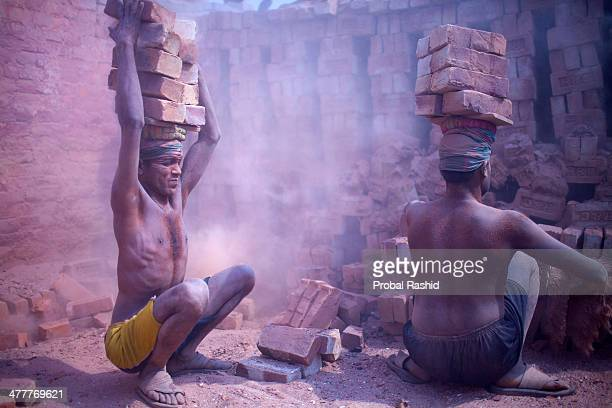 Bangladeshi daily labourers pile up bricks on their heads in a brick field at Gazipur Most of the daily labourers have migrated from different parts...