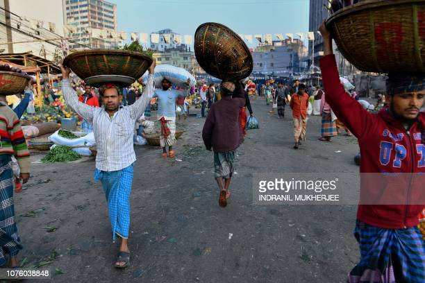 Bangladeshi delivermen carry goods in baskets at a local market early morning in Dhaka on December 31 a day after the country's general election...