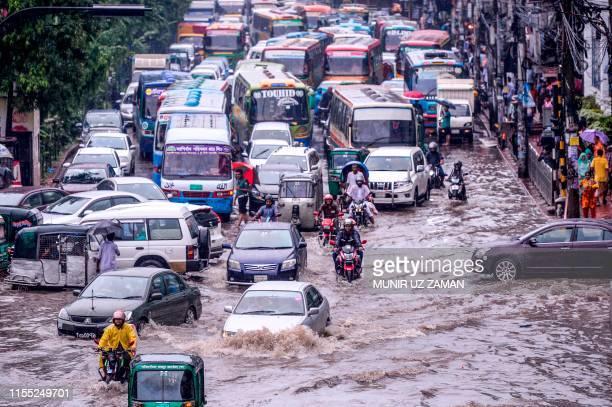 Bangladeshi drivers make their way through heavy rainfall at a waterlogged street during the monsoon season in Dhaka on July 12 2019