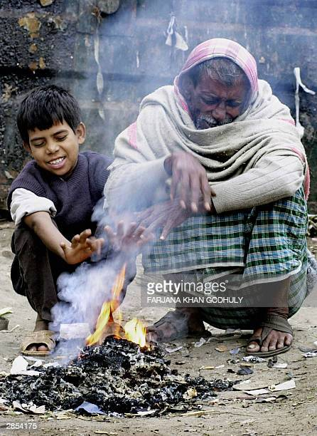 Bangladeshi elderly man Chan Mia and his grandson Monir Mia warm their hands in front of a fire in Dhaka 09 January 2004 The death toll from a cold...