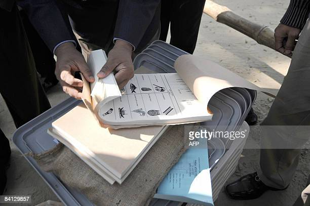A Bangladeshi election officer checks ballot papers after collecting them from the Election Commission in Dhaka on December 28 2008 Bangladesh goes...