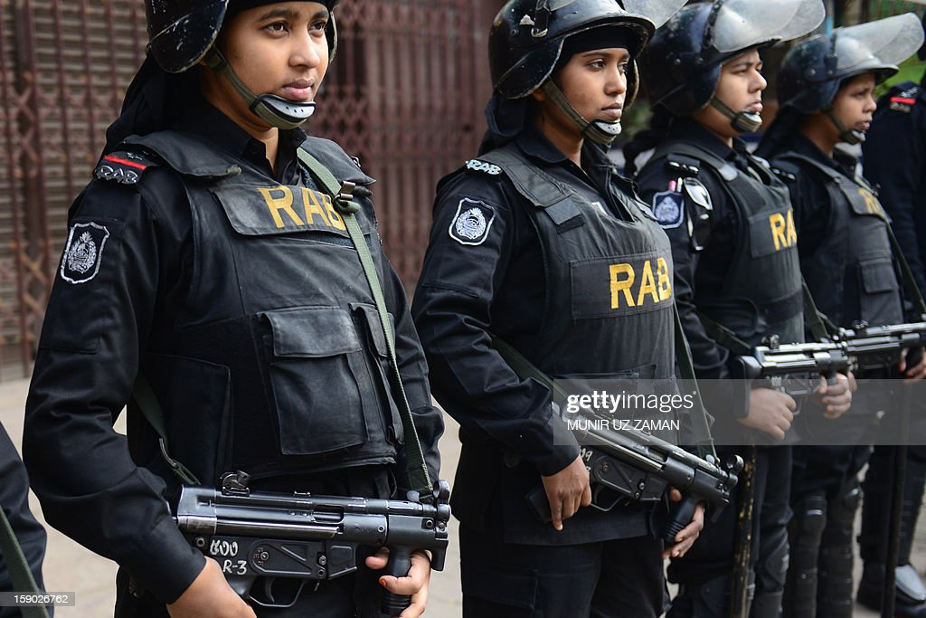 Bangladeshi elite force Rapid Action battalion (RAB) members stand guard in front of the Bangladesh Nationalist Party office during a nationwide strike in Dhaka on January 6, 2013. Anti-government protesters set fire to cars and buses during the opposition alliance's day-long countrywide shutdown strike protesting the latest hike in fuel oil prices. AFP PHOTO/ Munir uz ZAMAN