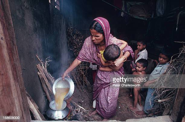 Bangladeshi family cooks lunch in the store room that they have made their home after their flimsy bamboo house was blown away by the recent cyclone...
