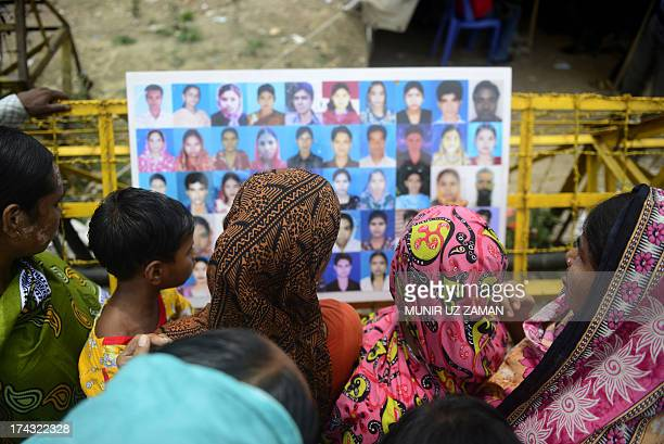 Bangladeshi family members and supporters look at a photographic installation of portraits of garment workers who worked in the collapsed building on...