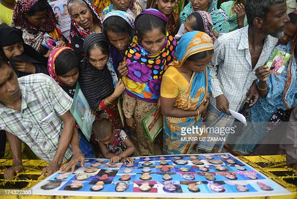 Bangladeshi family members and supporters look at a photographic installation of portraits of garment workers who had worked in the collapsed...