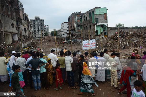 Bangladeshi family members of missing garment workers and onlookers gather at the site of the April 2013 nine-storey building collapse in Savar, on...